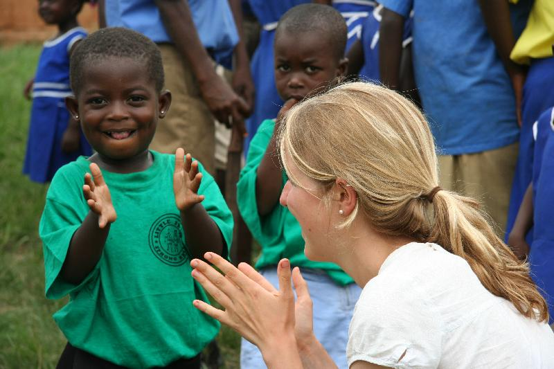 An intern and a child clap hands during an activity on our Social Work internship in Ghana